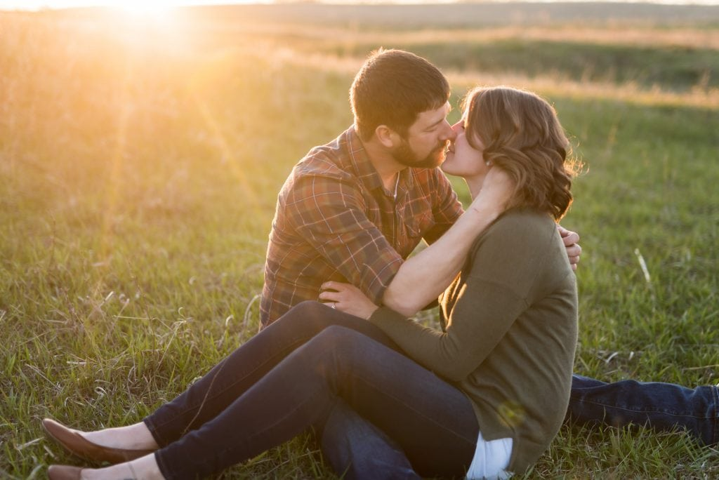 Couple sitting close together and kissing in an ND prairie - Chelsea Joy Photography