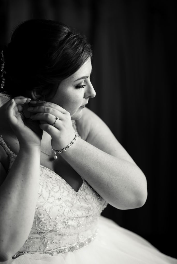 Bride adjusting her earrings - Chelsea Joy Photography