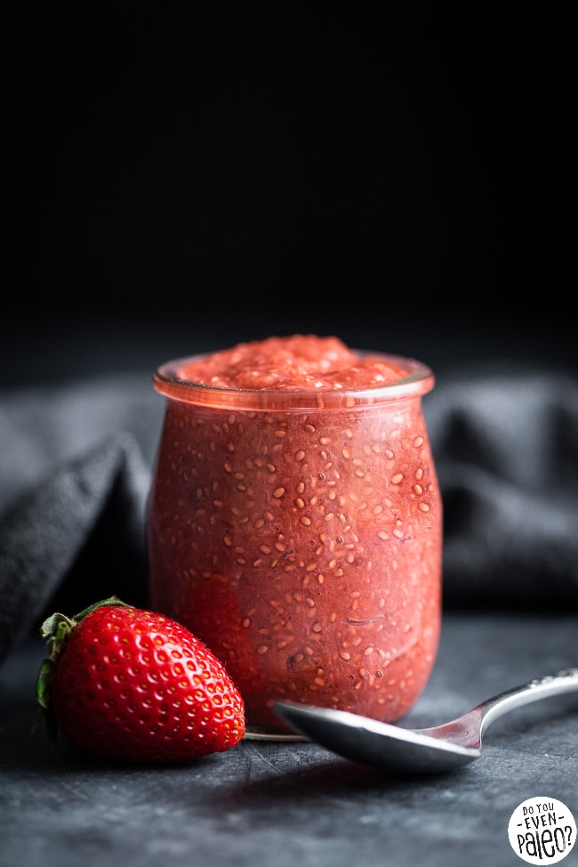 Jar of strawberry rhubarb chia seed jam with spoon and strawberries