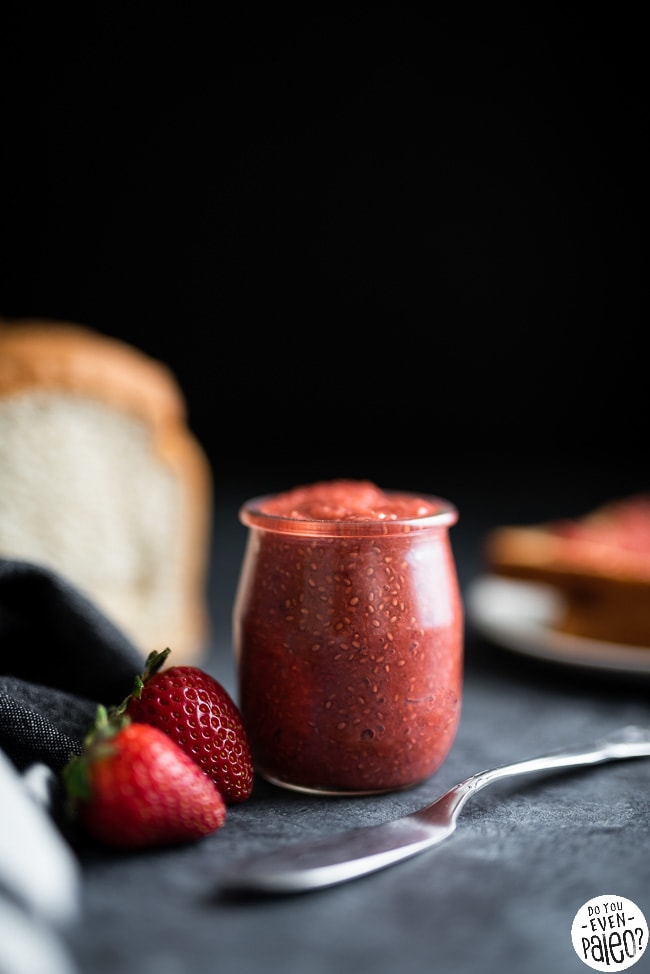 Jar of strawberry rhubarb chia seed jam with a loaf of bread and toast in the background