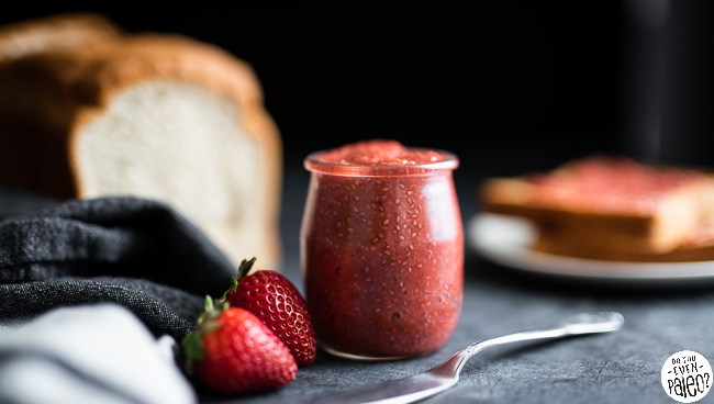 Small jar of strawberry rhubarb chia seed jam with loaf of gluten free bread and toast