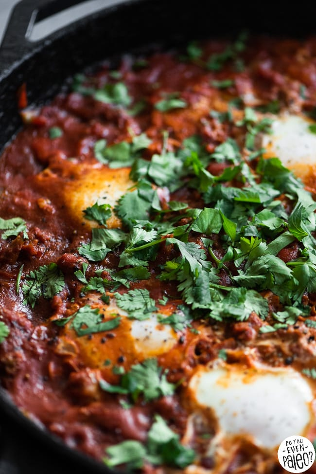 Cast iron skillet with chorizo shakshuka garnished with cilantro