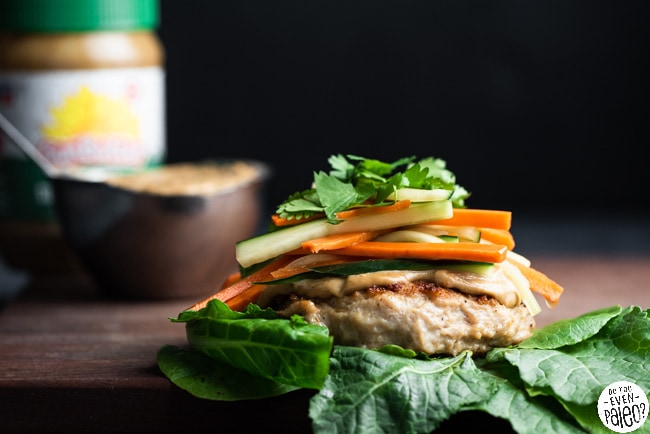 Paleo chicken patty on a bed of lettuce, topped with SunButter sauce and veggies.