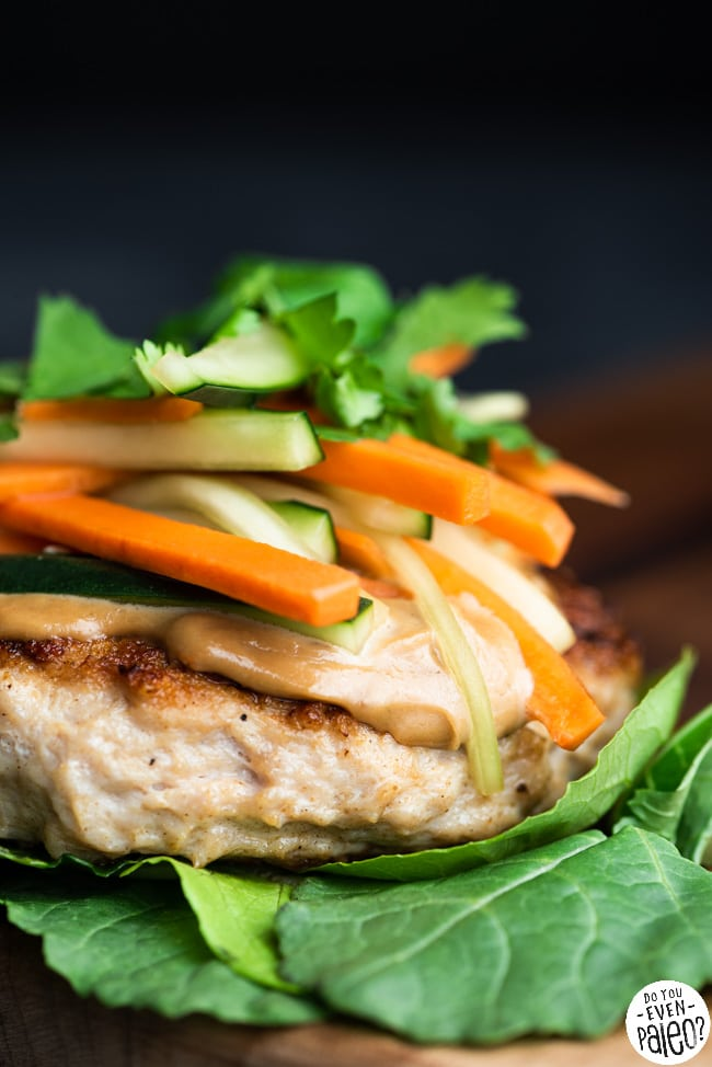 Closeup of a Whole30 chicken burger on a bed of greens, topped with SunButter sauce and veggies