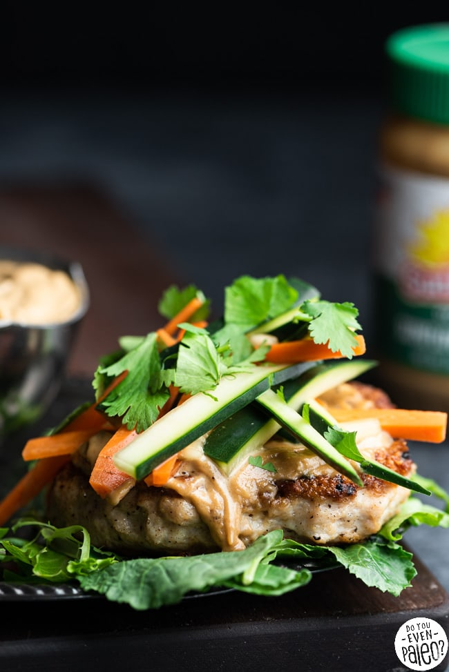 Chicken burger on a bed of lettuce, topped with SunButter sauce and veggies.