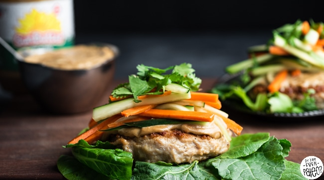 Chicken burgers on a bed of lettuce, topped with SunButter sauce and veggies