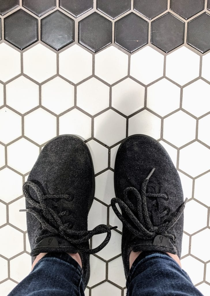 black Allbirds shoes on subway tile flooring