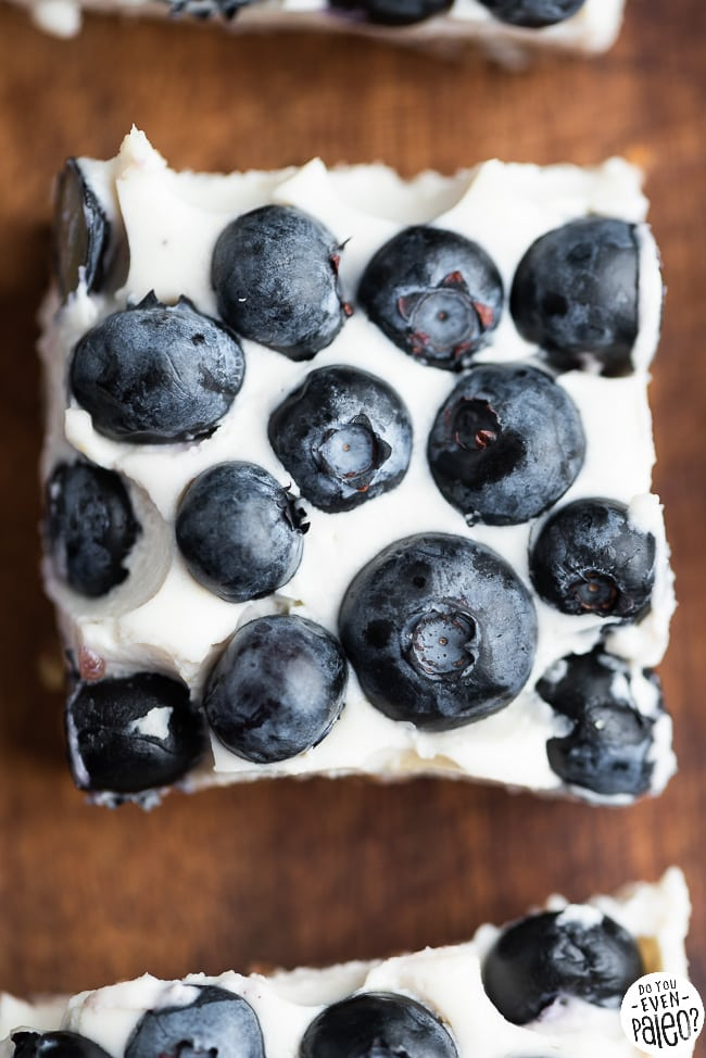 Closeup of no bake lemon blueberry cheesecake bar on a wooden cutting board