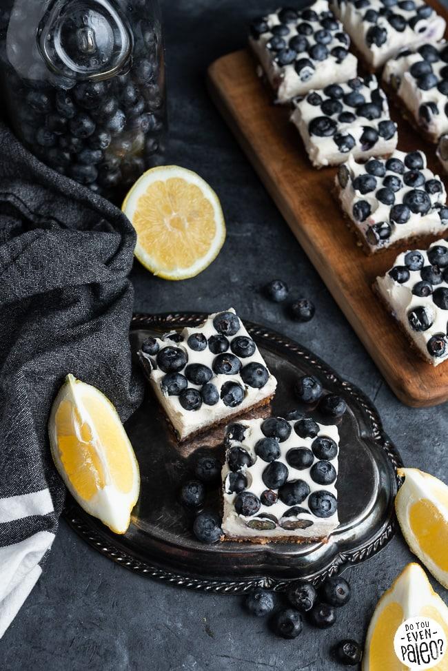 Paleo lemon blueberry cheesecake bars styled on a dark background