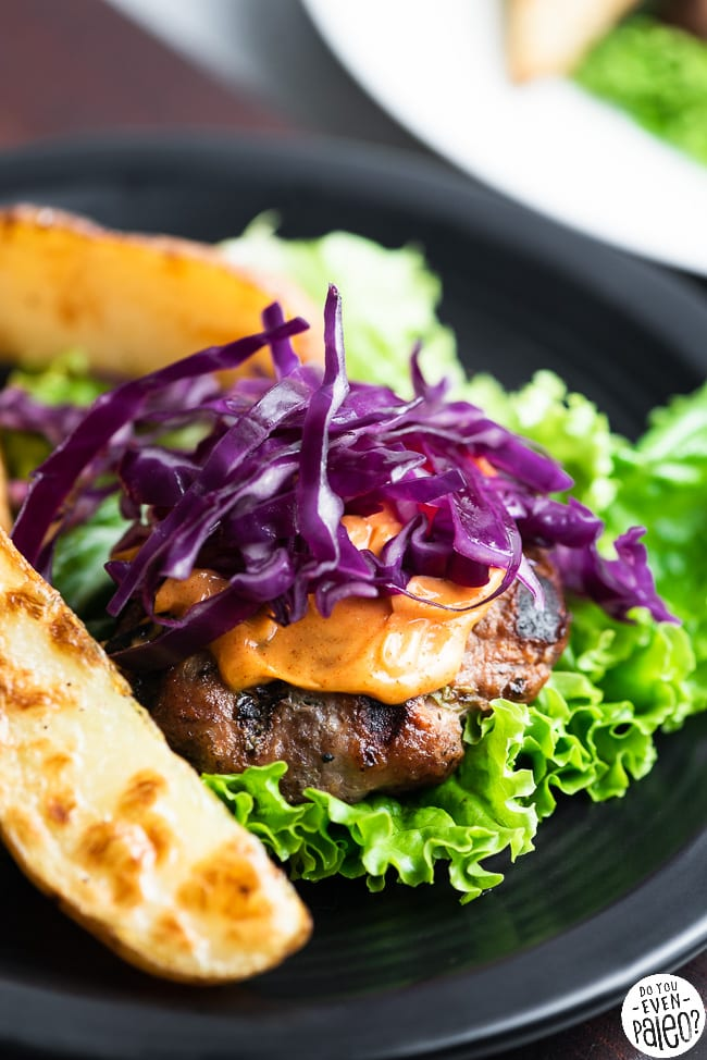Paleo Asian pork burger garnished with mayo and cabbage on a black plate
