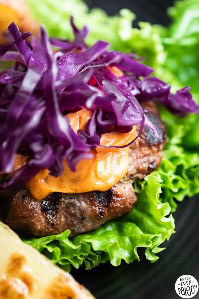 Closeup of bunless burger garnished with lettuce, mayo, and cabbage slaw