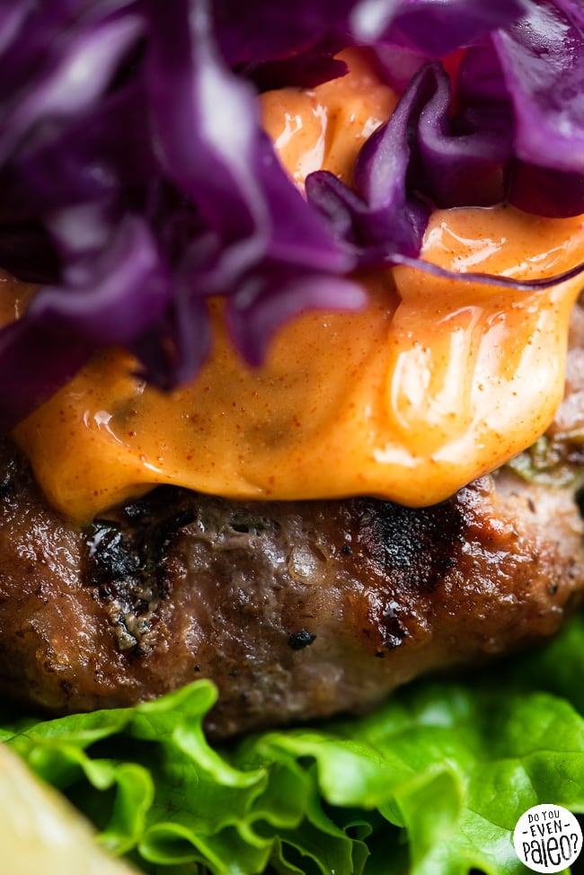 Closeup of a pork burger topped with chili mayo and red cabbage