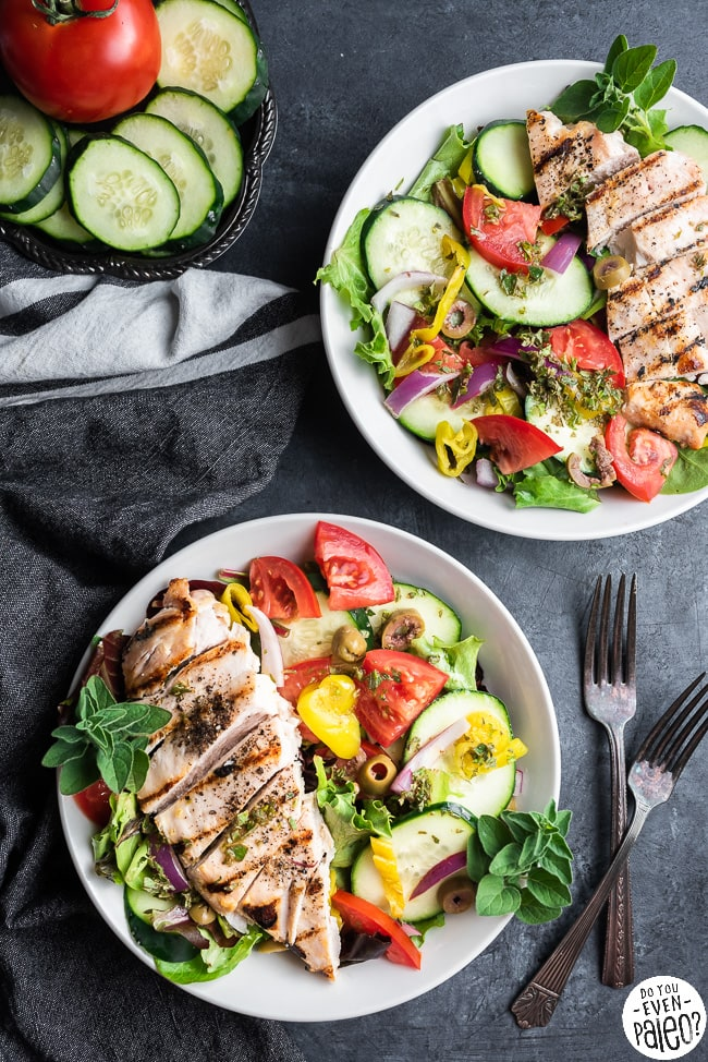 Two bowls filled with Greek salad and grilled chicken
