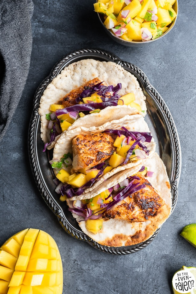 Paleo fish tacos on a tray surrounded by mangoes and limes