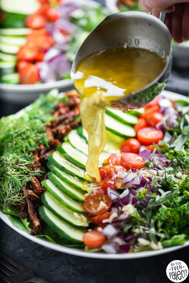 Closeup of hand pouring salad dressing on a chopped salad