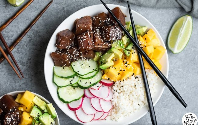 Paleo Ahi Tuna Poke Bowl garnished with sesame seeds and lime wedges