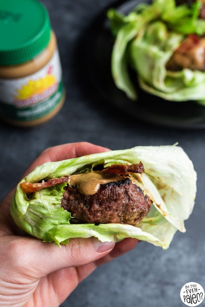 Hand holding a lettuce-wrapped SunButter bacon burger