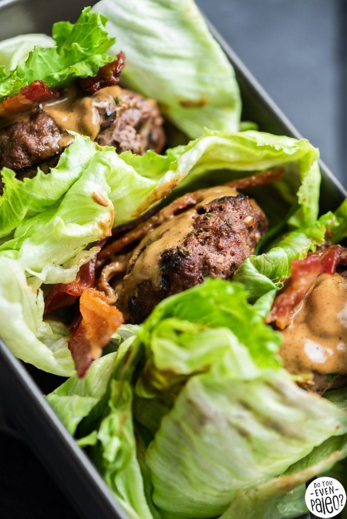 Three lettuce-wrapped SunButter bacon burgers presented in a loaf pan