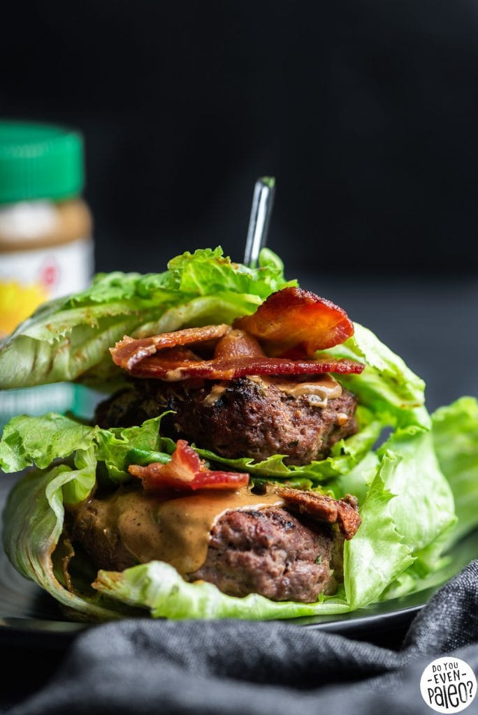Two lettuce-wrapped SunButter bacon burgers stacked on top of each other