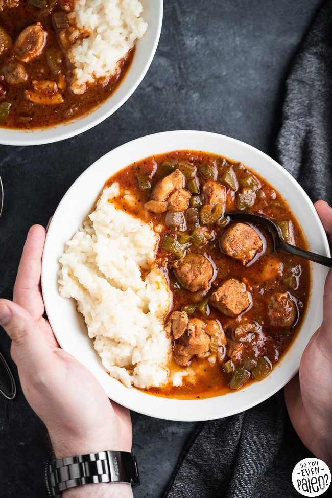 Hands holding a bowl of gumbo with rice
