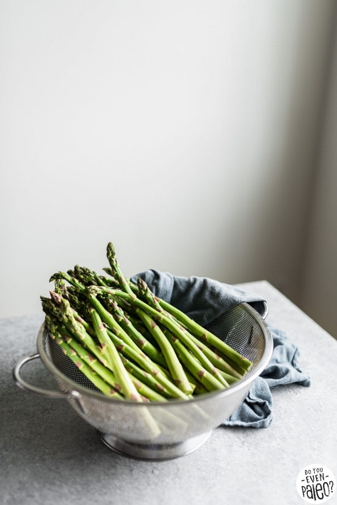 Asparagus in a colander on a countertop
