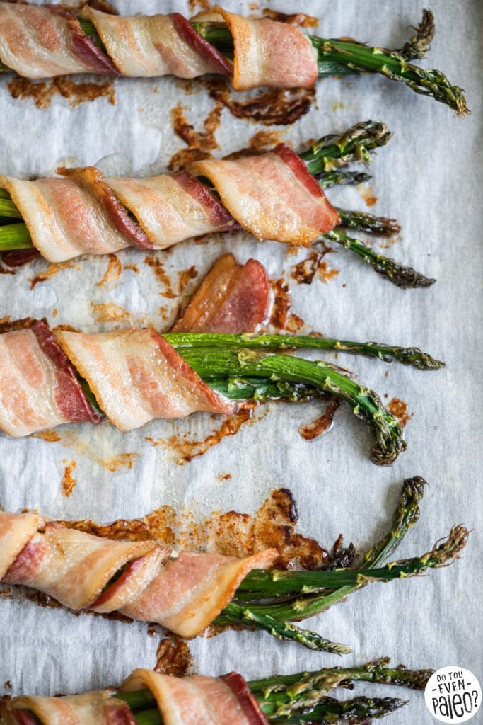Asparagus bundles wrapped in bacon on a baking sheet