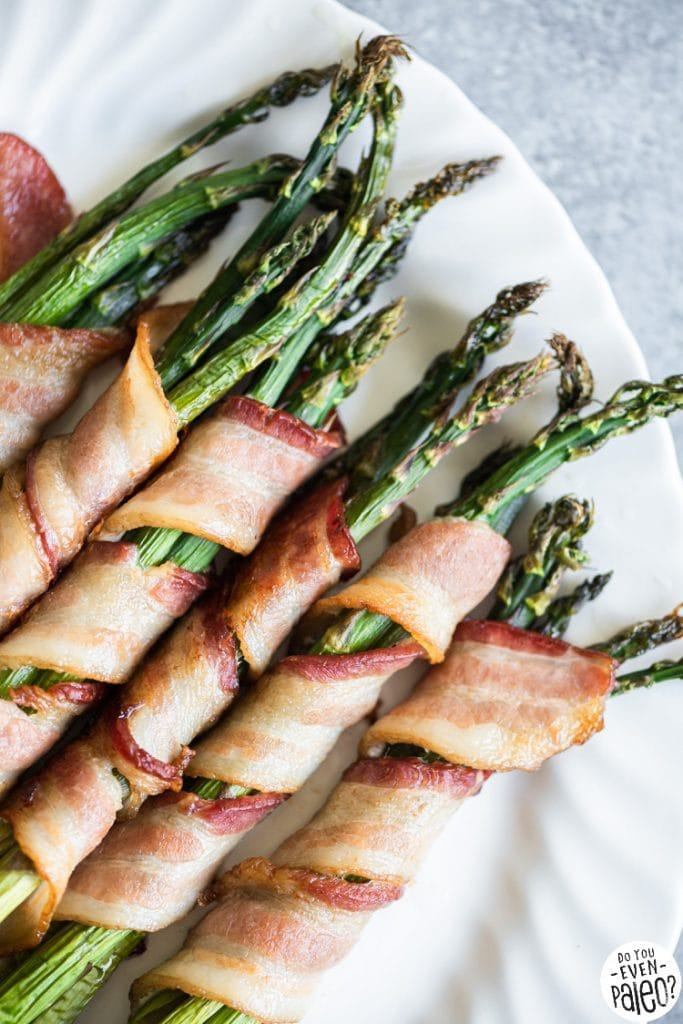 Closeup of bacon-wrapped asparagus on a white serving plate