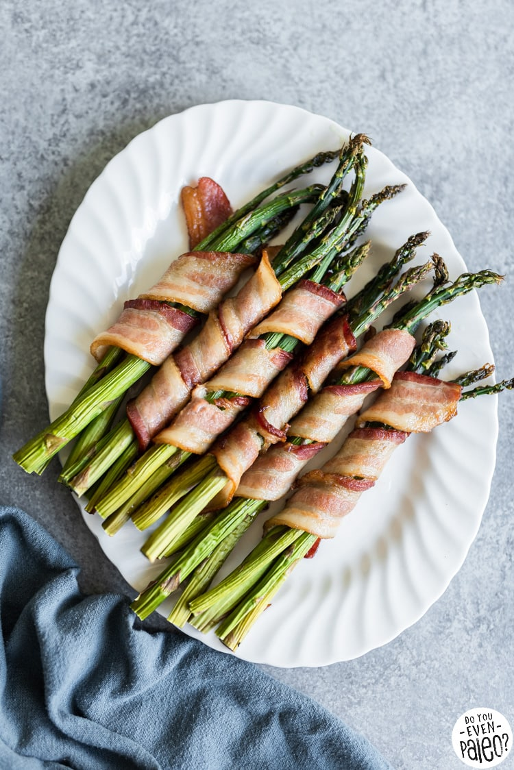 Bacon-wrapped asparagus bundles on a white serving tray