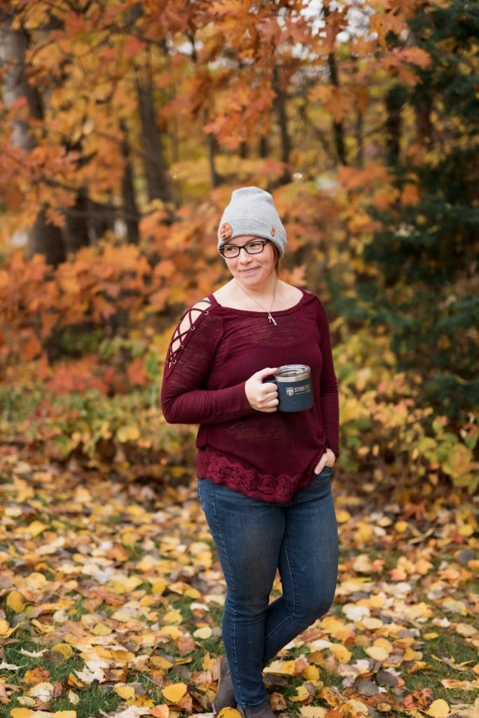 Portrait of a woman holding a travel coffee mug, surrounded by fall foliage