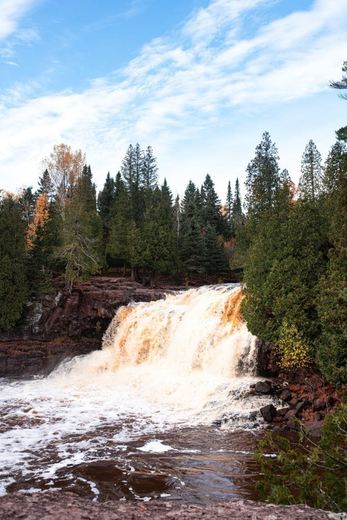 Waterfall at Gooseberry Falls State Park surrounded by trees in autumn