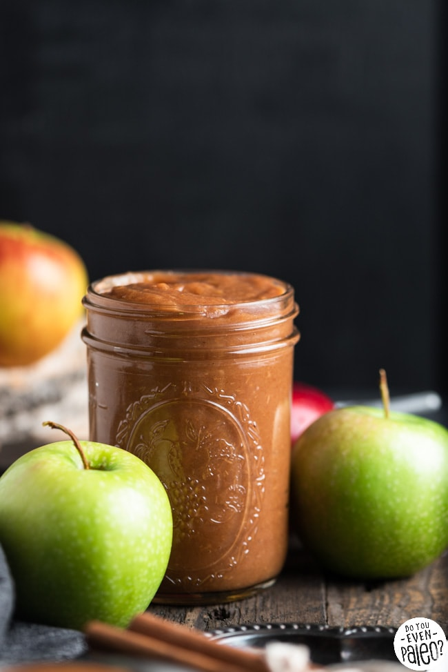 Mason jar full of homemade apple butter surrounded by various apples