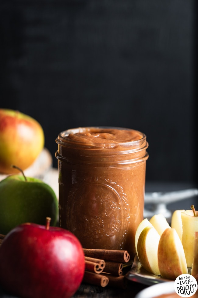 Mason jar full of homemade apple butter, surrounded by various apples