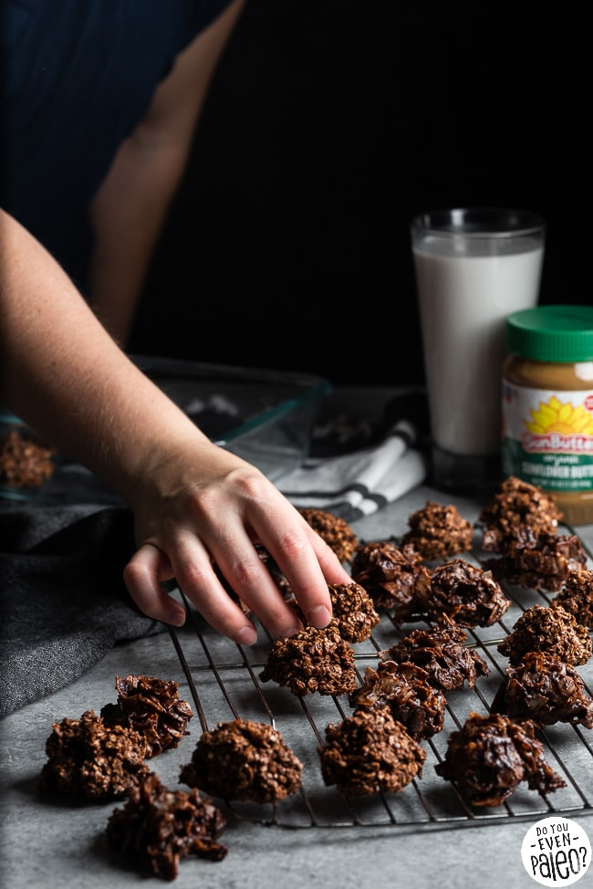 Woman's hand taking a SunButter no bake cookie off of a cooling rack full of cookies