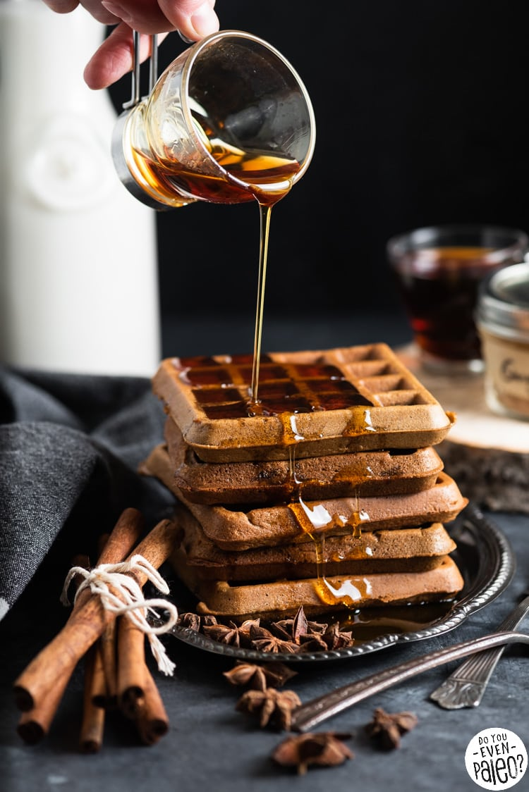 Person pouring maple syrup onto a stack of gingerbread waffles