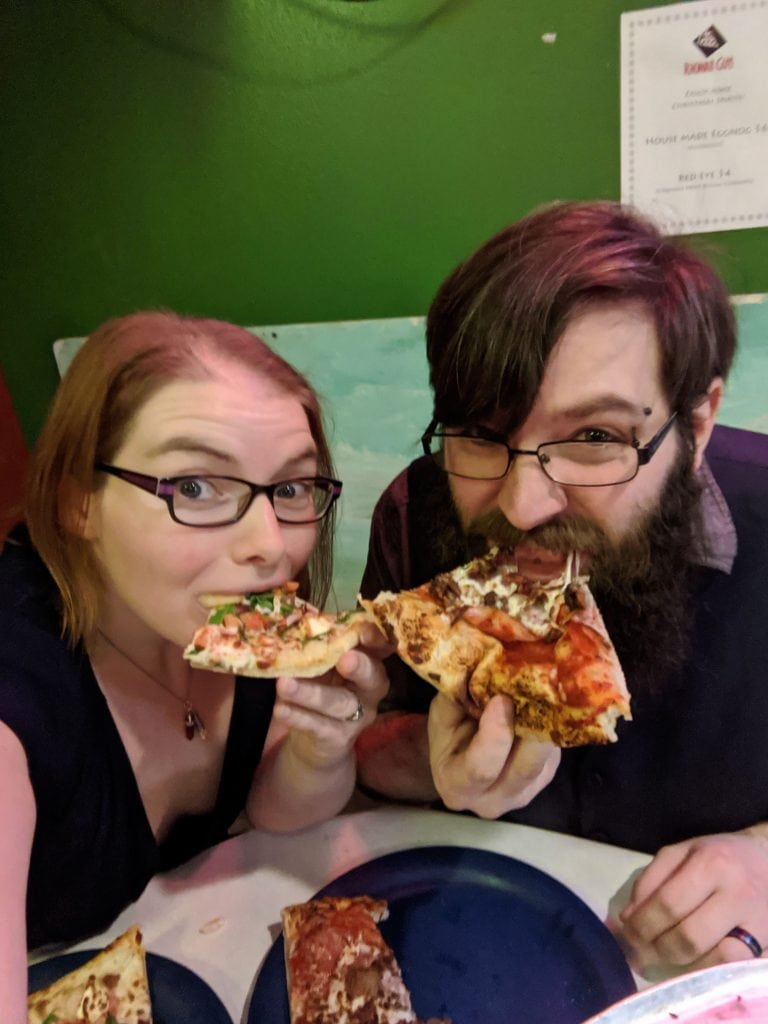 Couple eating pizza at Rhombus Guys pizza