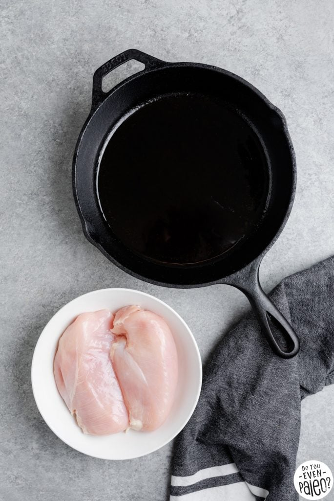 A large deep-bottomed skillet and a bowl with two uncooked chicken breasts