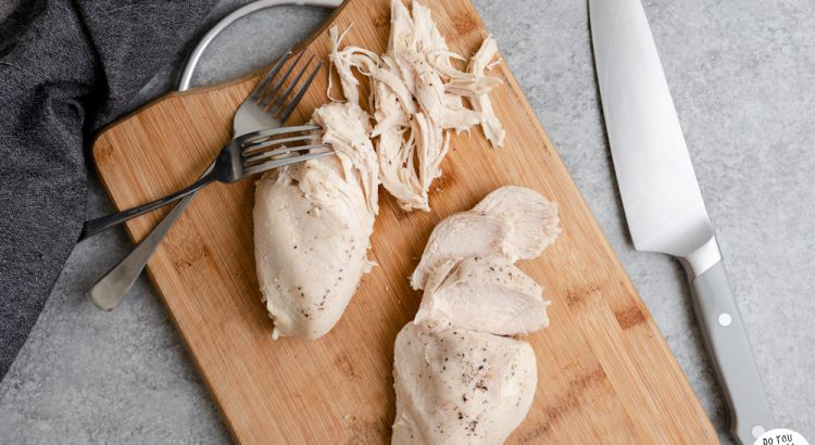 Poached chicken breasts on a cutting board