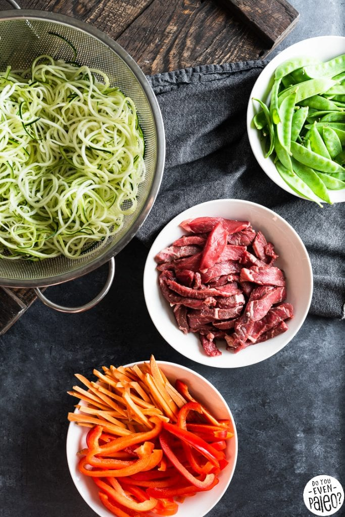 Bowls containing veggies and raw beef