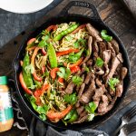 Skillet full of Thai Beef Stir Fry with zucchini noodles and SunButter sauce