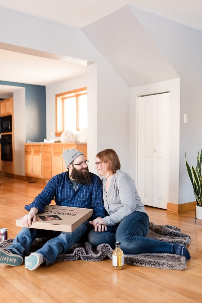 A couple sitting on the floor of an otherwise empty house
