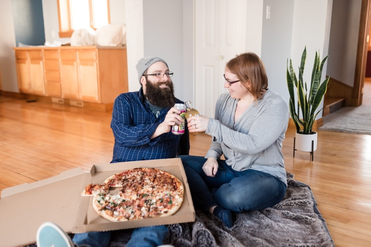 A couple clinking glasses and sharing a pizza in an otherwise empty house