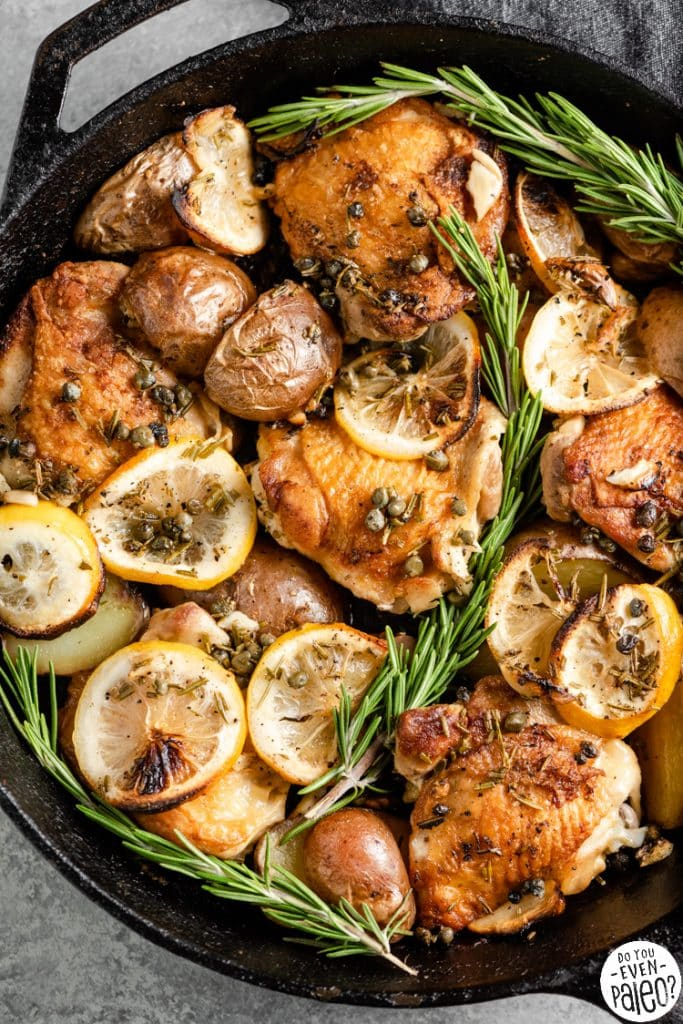 Closeup of a cast iron skillet filled with lemon rosemary chicken thighs and potatoes