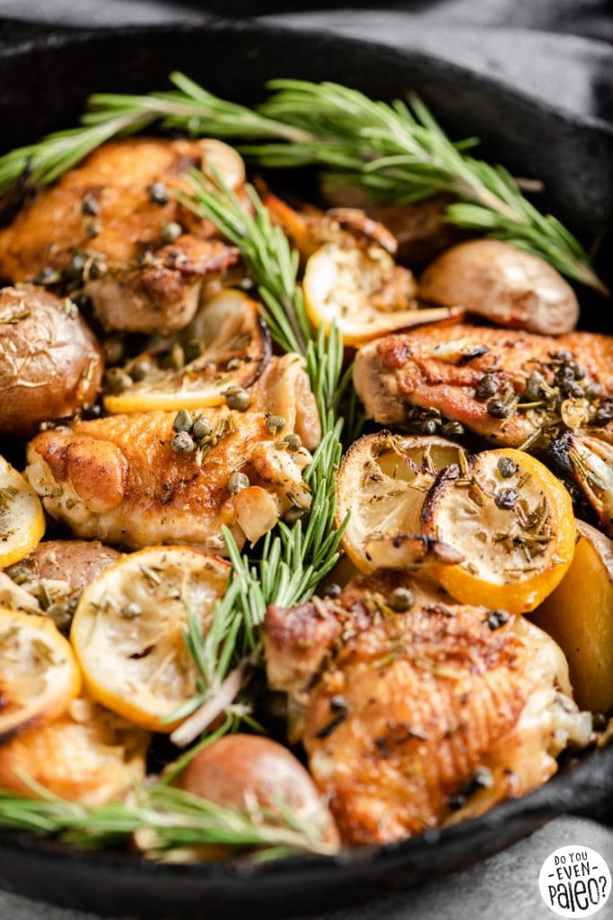 Closeup of lemon rosemary chicken thighs and potatoes in a cast iron skillet
