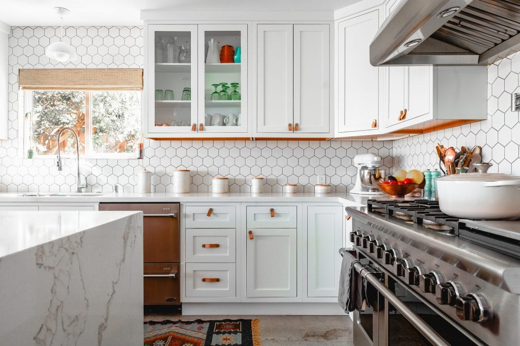 A clean, white environmentally friendly kitchen with wood accents