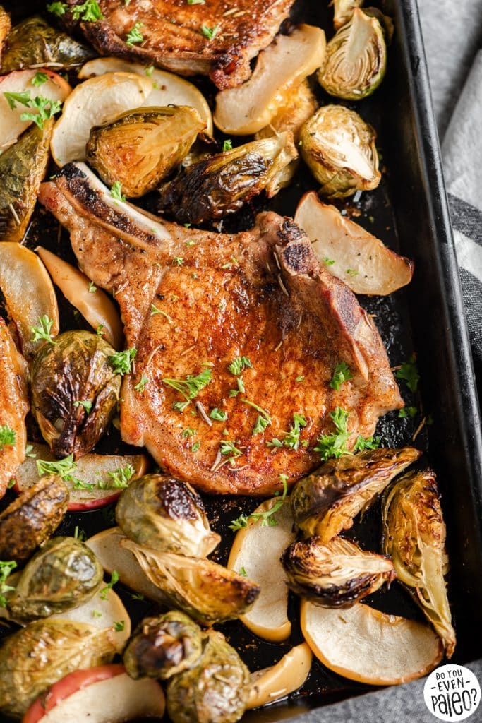 Closeup of pork chops and vegetables on a sheet pan
