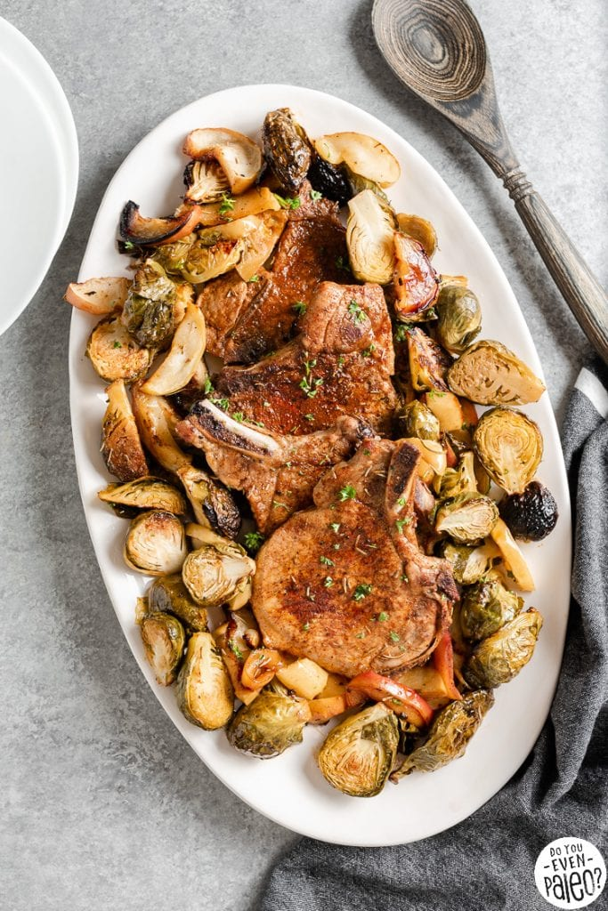 Sheet pan pork chops with brussels sprouts and apples on a serving platter