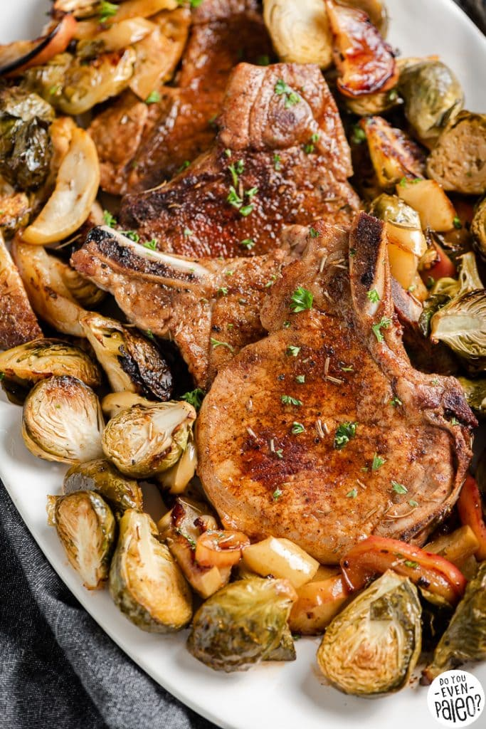 Closeup of cooked pork chops with brussels sprouts and apples