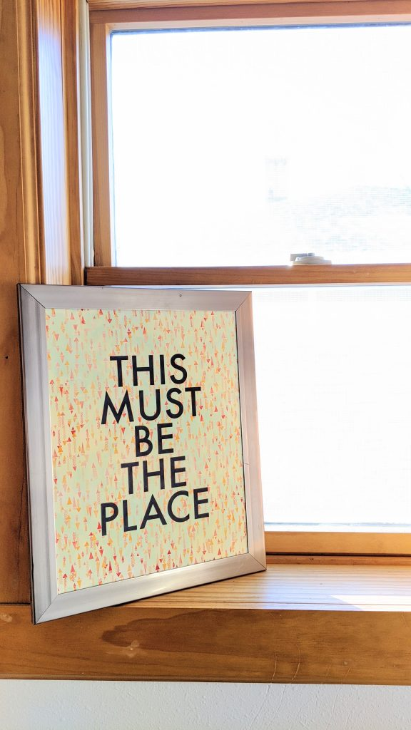 "Framed print on a windowsill reading ""This Must Be The Place"""
