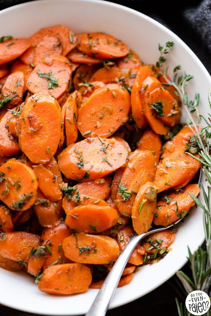 Closeup of herbed garlic carrots with a serving spoon