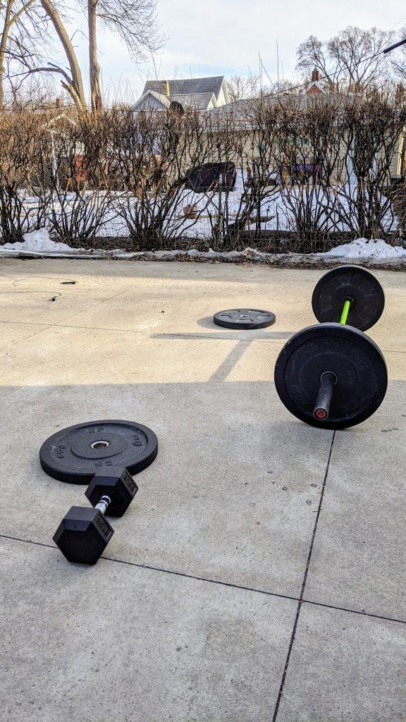 A barbell, dumbell, and bumper plates on a driveway